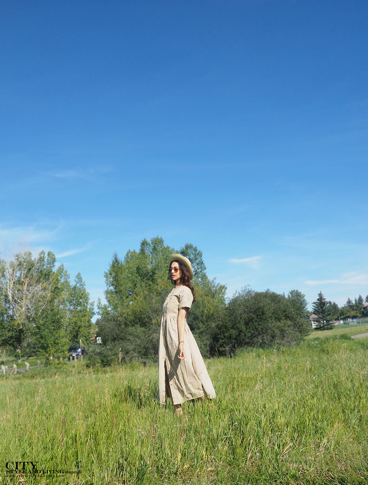 The Editors Notebook calgary fashion blogger wearing a khaki dress and straw hat at glenmore walking in field