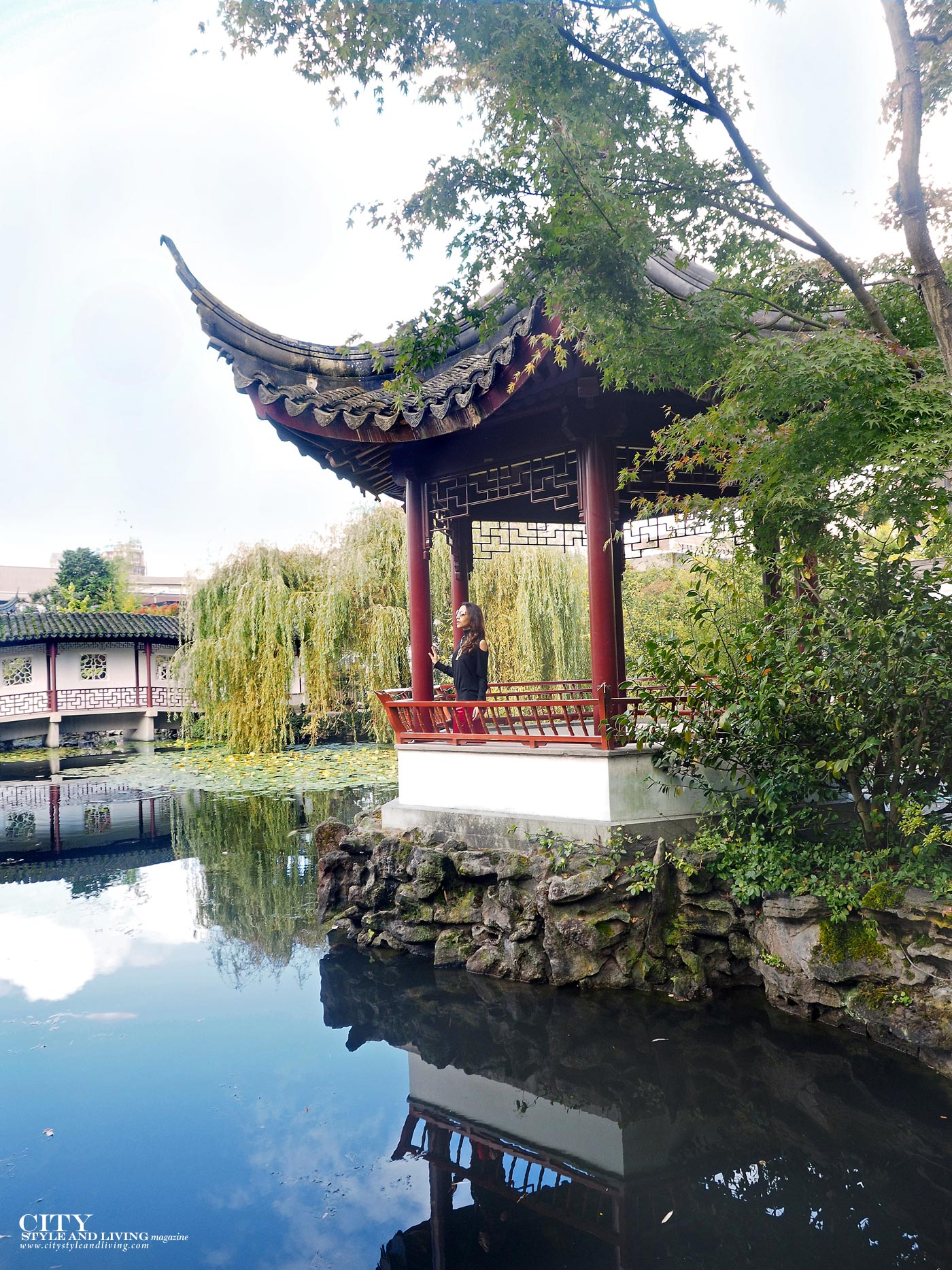 City Style and Living The Editors Notebook style blogger Shivana M  at Dr. Sat Yuen Sen Chinese Gardens in Vancouver wearing a cashmere top and red cropped pants walking pagoda by water