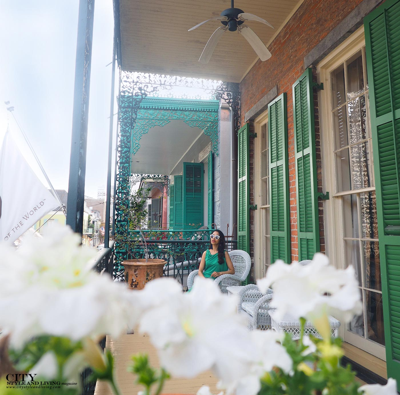 BalconCity style and living magazine The Editors Notebook style fashion blogger Shivana Maharaj French Quarter New Orleans Soniat House Balcony wearing BCBG Max Azria green maxi dress sitting with flowersyFlowerswatermark