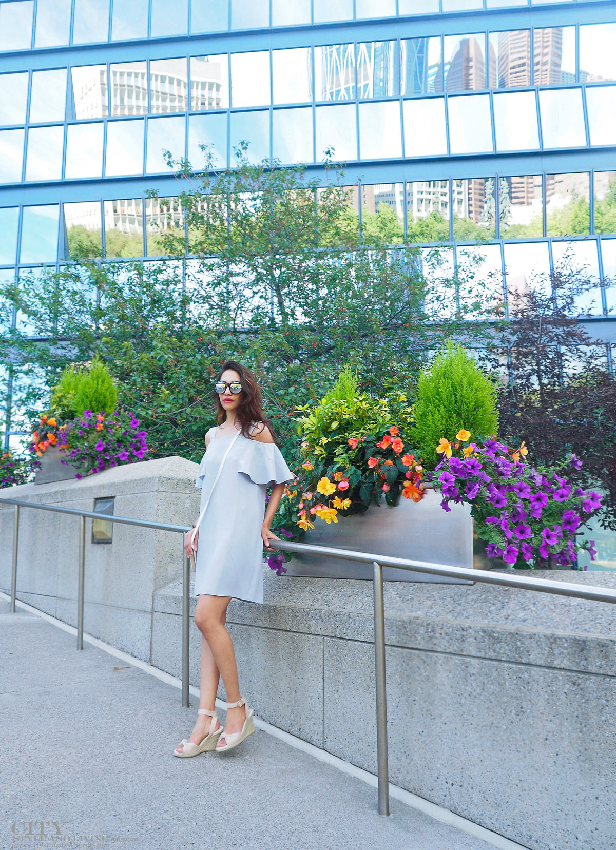 City STyle and Living The Editors Notebook style blogger Downtown Calgary standing colourful flowers blooming during summer wearing an off shoulder topshop dress and wedges