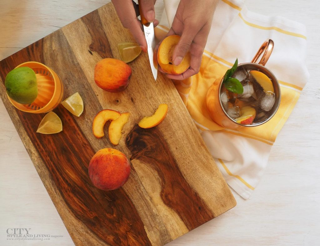 City Style and Living Magazine peach moscow mule hand slicing peach